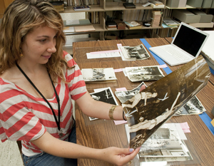 Undergraduate intern Rachel Platis selects photographs for a forthcoming exhibition. Photo by Pete Smith.