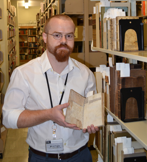 Ransom Center Project Archivist Micah Erwin holds one of the books with manuscript fragments that he's hoping to identify through a Flickr site he created. Photo by Alicia Dietrich.