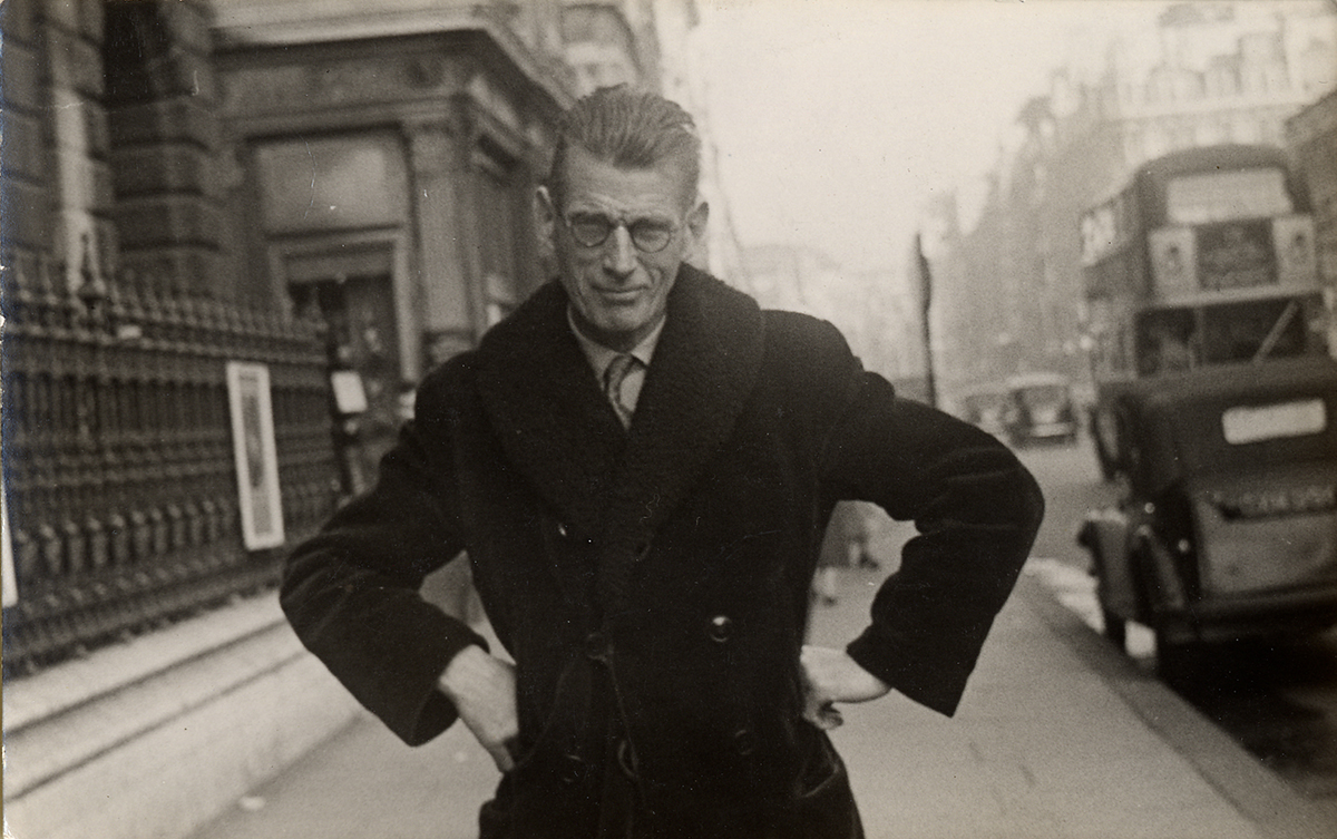 Photograph of Samuel Beckett taken by a street photographer outside Burlington House in Piccadily, ca. 1954.