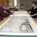 "Associate Director for Conservation and Building Management Jim Stroud and Hamilton carefully roll a protective layer of paper on top of the Giovanni Battista Piranesi's enormous 1786 print ""Pianta delle Fabriche Esistenti Nella villa Adriana."" Hamilton created a housing to safely store and make the 10-foot wide map of Hadrian's villa accessible to scholars and students. Photo by Pete Smith."