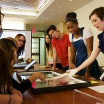 """Teacher Andrea Gustavson shares photography materials with undergraduate students in her class """"American Images: Photography, Literature, Archive"""" Photo by Robert V. Reichle."""