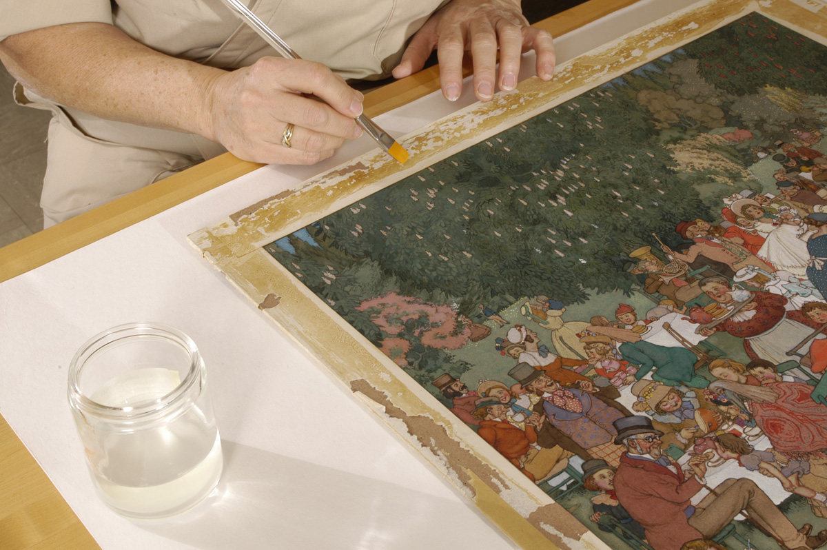 "Softening adhesive on the border of the drawing, ""The Christening Party"" by W. H. Robinson. Photo by Eric Beggs."