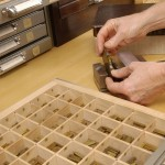 Setting brass type in a pallet to stamp a label for a book. Photo by Eric Beggs.