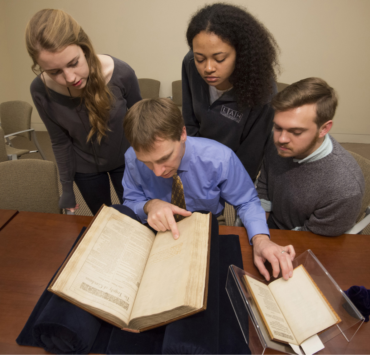 "Elon Lang, seated in the center, and undergraduates from ""Drama in the Archives"" view collection materials. Students, clockwise from upper left, are Lily Pipkin, Haley Williams, and Kenneth Williams. Photo by Pete Smith."