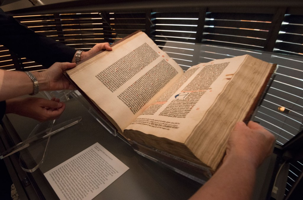 Conservators turn the pages to display the Book of Ezekiel in the Gutenberg Bible. Photo by Pete Smith.