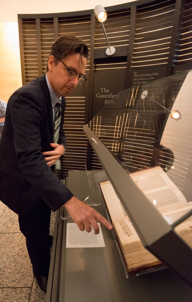 Gerald Cloud inspects the newly turned page of the Gutenberg Bible. Photo by Pete Smith.