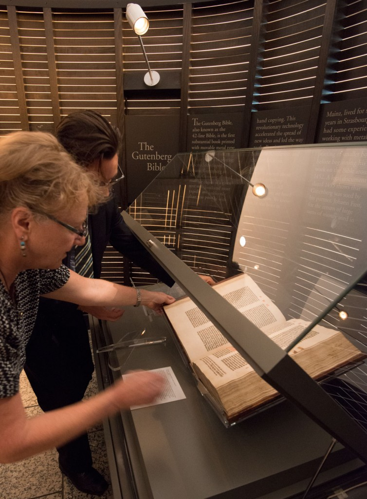 Ransom Center staff place the Gutenberg Bible in the display case with exhibition label. Photo by Pete Smith.