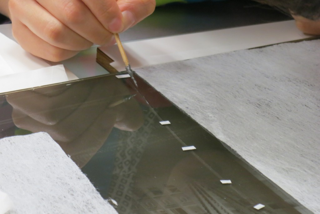 Application of the adhesive to the glass plate.