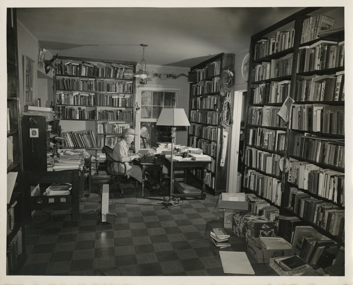 8.Bill Malone Photography. Photograph of J. Frank Dobie in his office, 1955. Dobie's office contents confirm that he was a keen collector of art, artifacts, and books concerned with Texas folklore, history, and language.