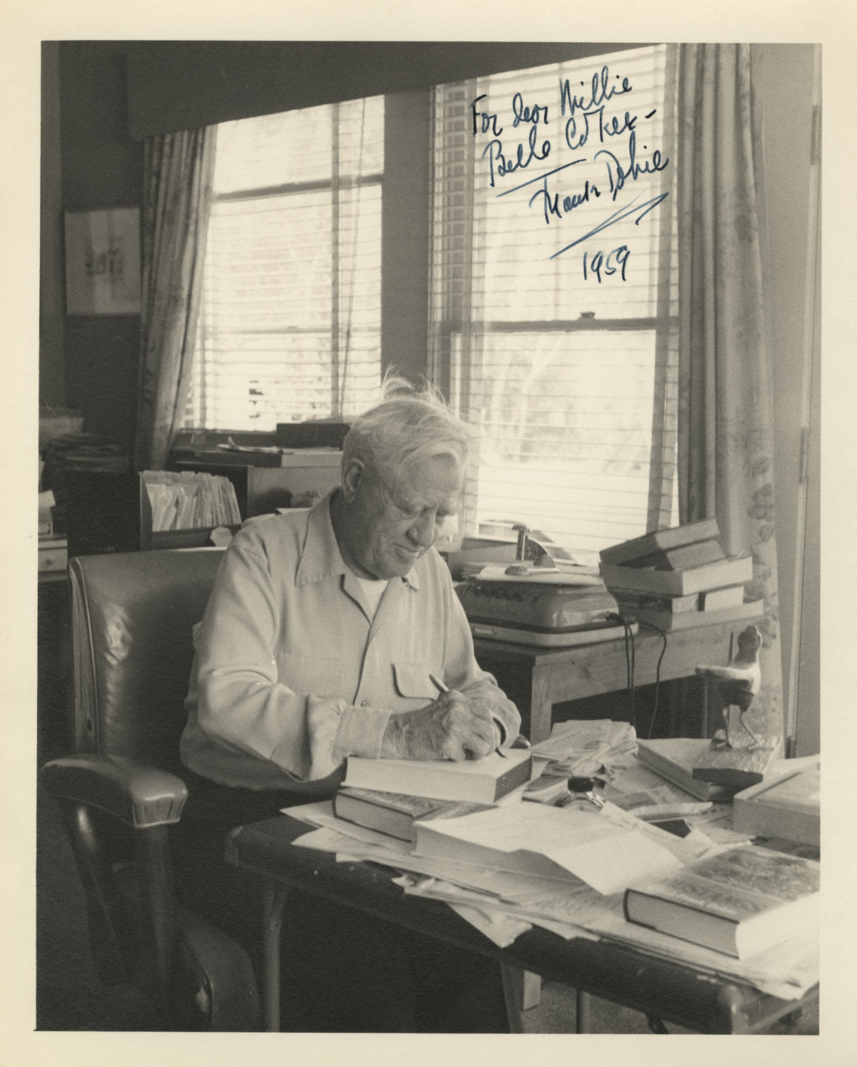 C. H. Dykeman, Photograph of J. Frank Dobie at his desk, 1959. Note the wooden roadrunner on his desk and the open file cabinet drawer showing folders of papers.