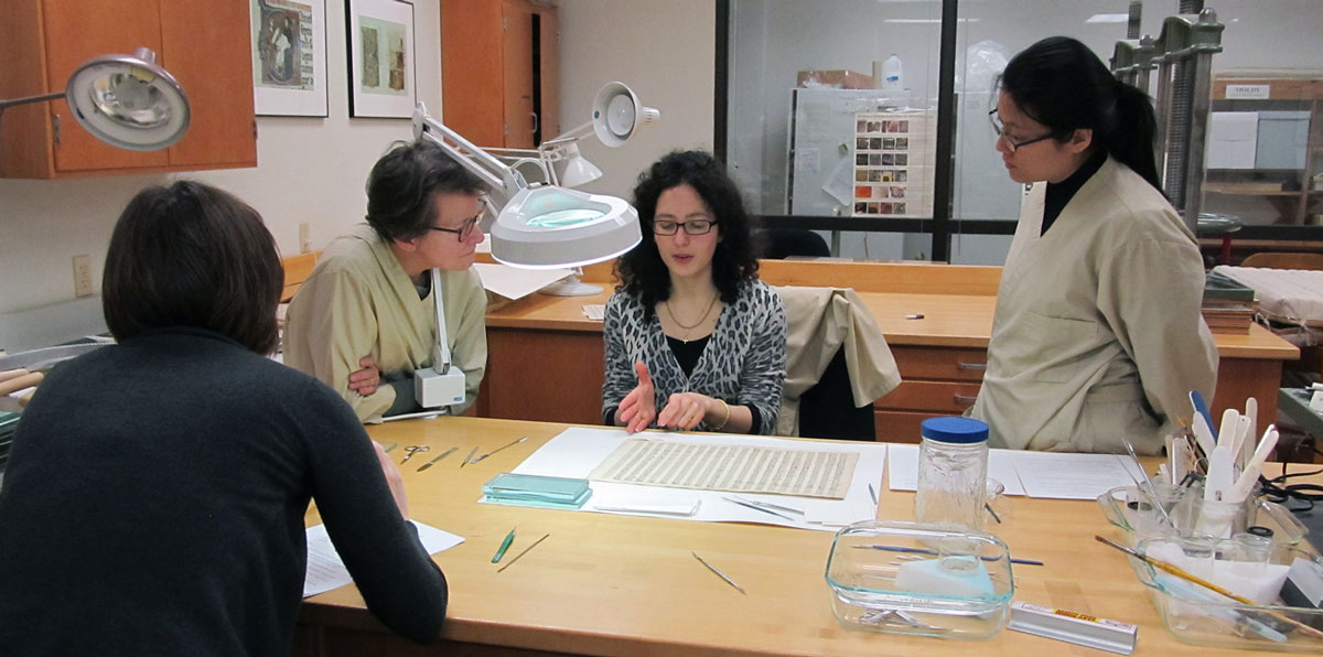 Conservators and volunteers discussing techniques for removing stiff paper repairs