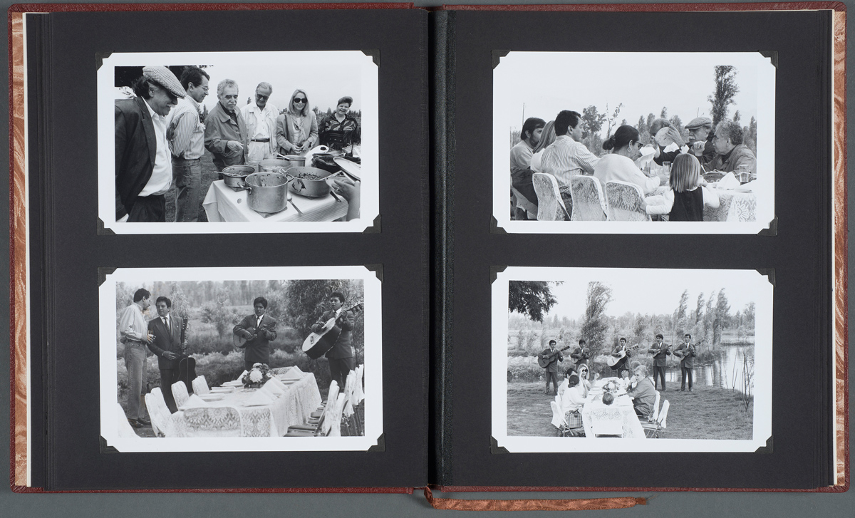 "An album labeled ""Un viaje de Xochimilco,"" opened to photographs of Gabriel García Márquez with author Carlos Fuentes and others, undated. Photographs by Fabrizio Leon."