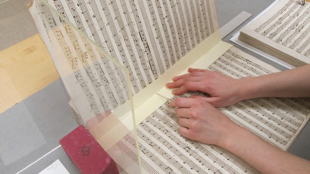 Préparation à coudre de nouveau le bloc-texte en pré-perçant les fonds de cahiers.