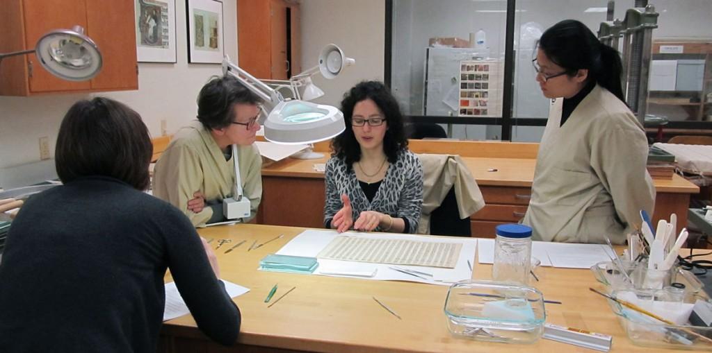 Discussion entre les conservateurs-restaurateurs et les volontaires sur les procédés de retrait des « réparations » en papier rigide.