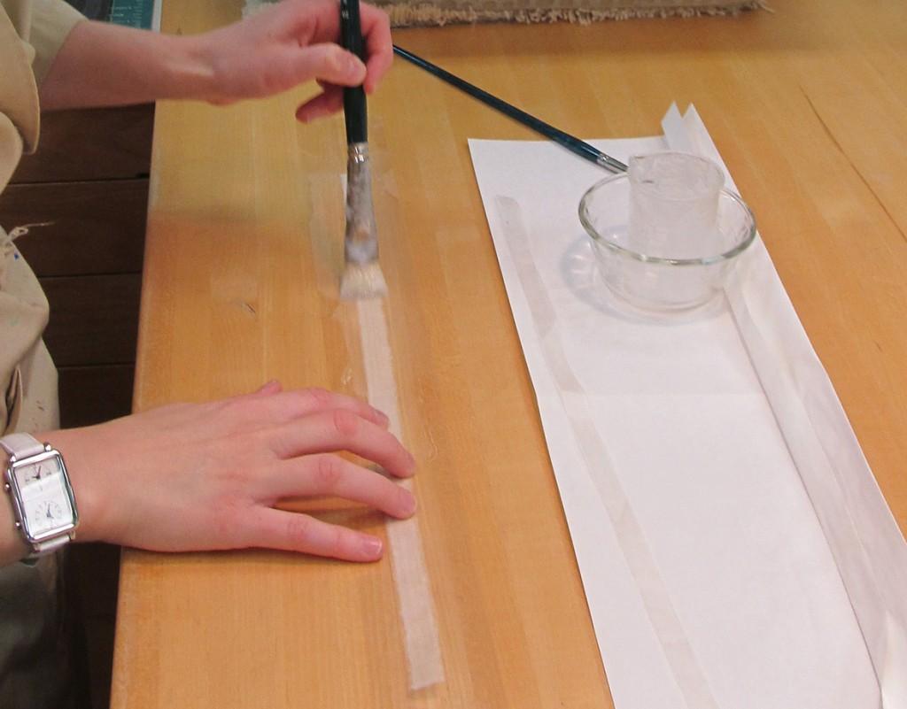 Application de colle de pâte d'amidon de blé Jin Shofu sur un onglet en papier japonais, constitué de fibres longues, afin de resolidariser les pages détachées au bloc-texte.