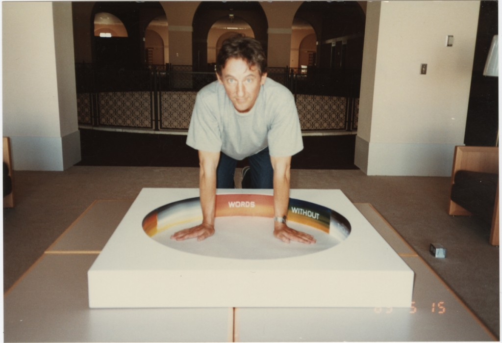 "Ed Ruscha at Miami-Dade Public Library with model for rotunda mural, 1985. Chromogenic color print, 14.8 x 10.1 cm. Throughout his career many have commissioned Ruscha to create an original piece of art for their publication, poster, or public space. In 1985, the Miami-Dade Public Art Council chose Ruscha out of a group of finalists to create a work for the newly constructed Miami-Dade Public Library. Ruscha's process from his proposal through to the installation and unveiling in the summer of 1985 are well documented through notes, contracts, plans, and photographs. Here Ruscha poses with a model of his concept: an eight-panel circular mural for the rotunda of the library. Each painted panel features a word in the following line from Shakespeare's Hamlet: ""Words without thoughts never to heaven go."""