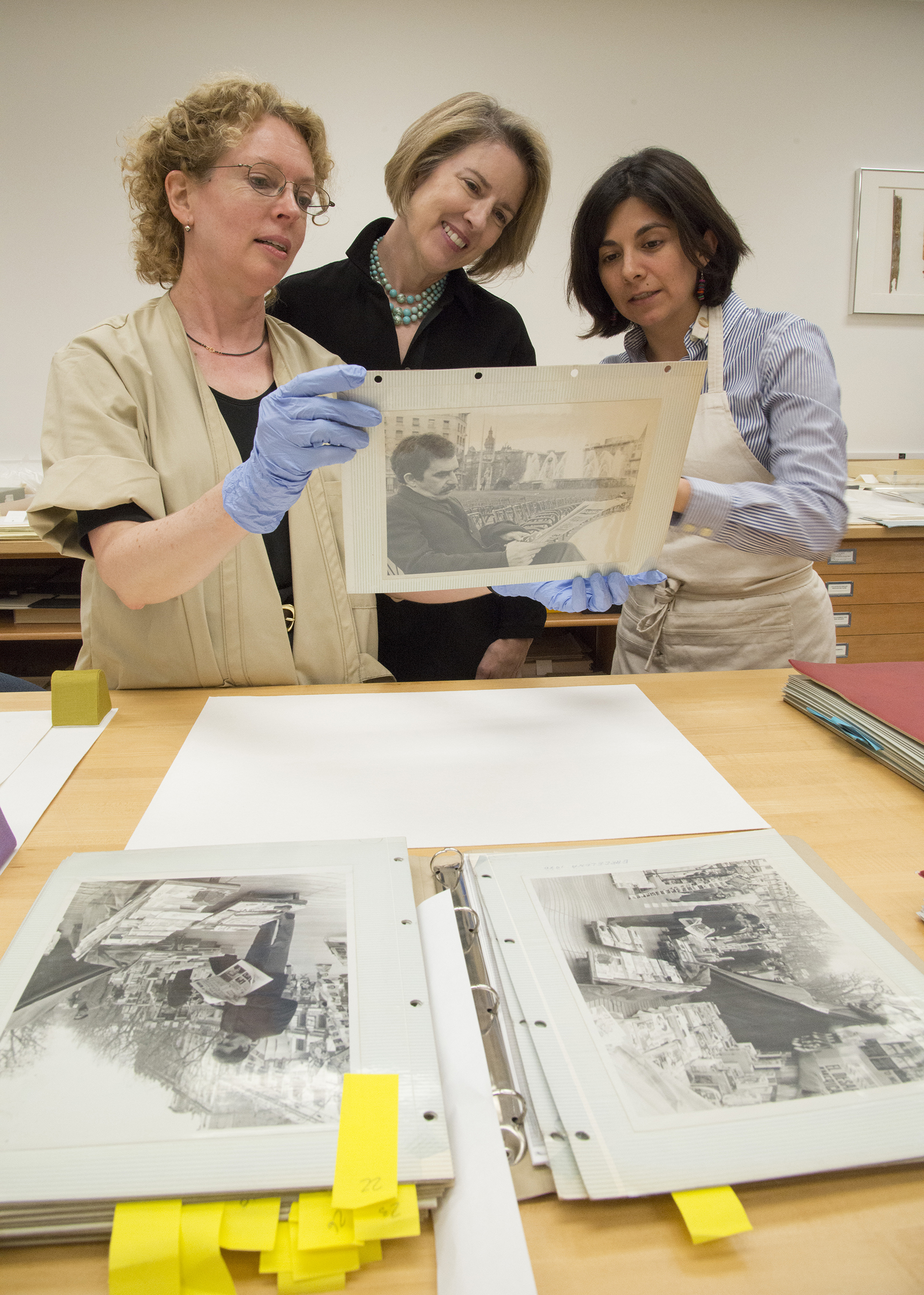 "Conservators Barbara Brown (L) and Diana Diaz (R) with Dr. Ellen Cunningham-Kruppa, Associate Director and Head, Conservation and Preservation Division, discussing issues of photographs stuck to ""magnetic"" album pages. Image courtesy of Harry Ransom Center."