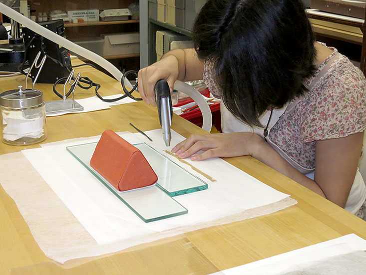 "Diana Diaz using the ""preservation pencil"" to detach the kraft-paper tape."