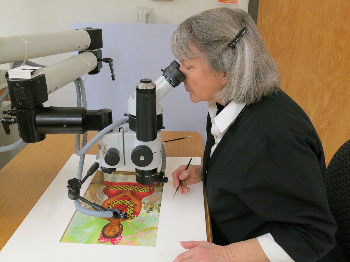 Assistant paper conservator Jane Boyd consolidates paint layers of a damaged Miguel Covarrubias gouache painting.