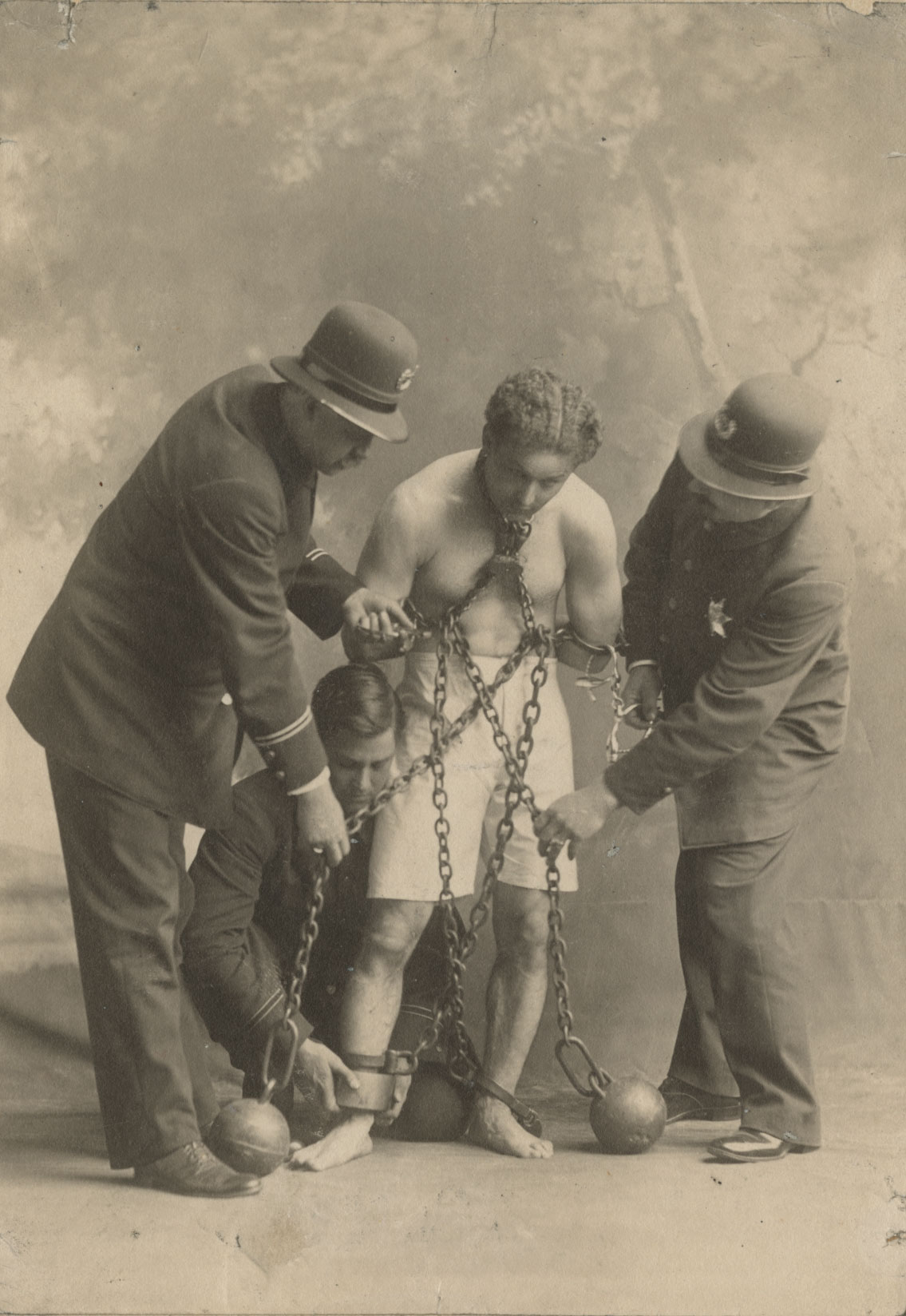Unidentified photographer, [Harry Houdini in chains and ball weights with police], ca. 1900. Gelatin silver print, 14 x 9.5 cm.