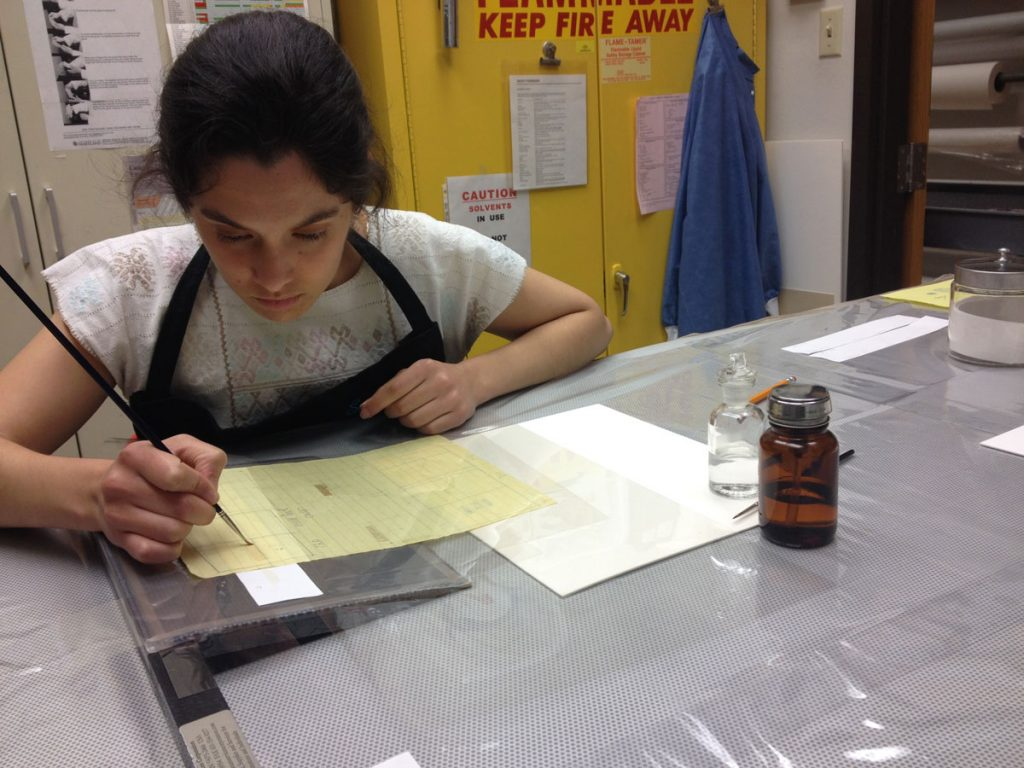 The author reducing the orange adhesive stains with solvents using the suction table.