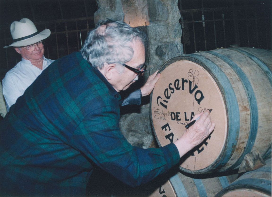 Gabriel García Márquez autographing a wine barrel, 2005. Photographer unknown.