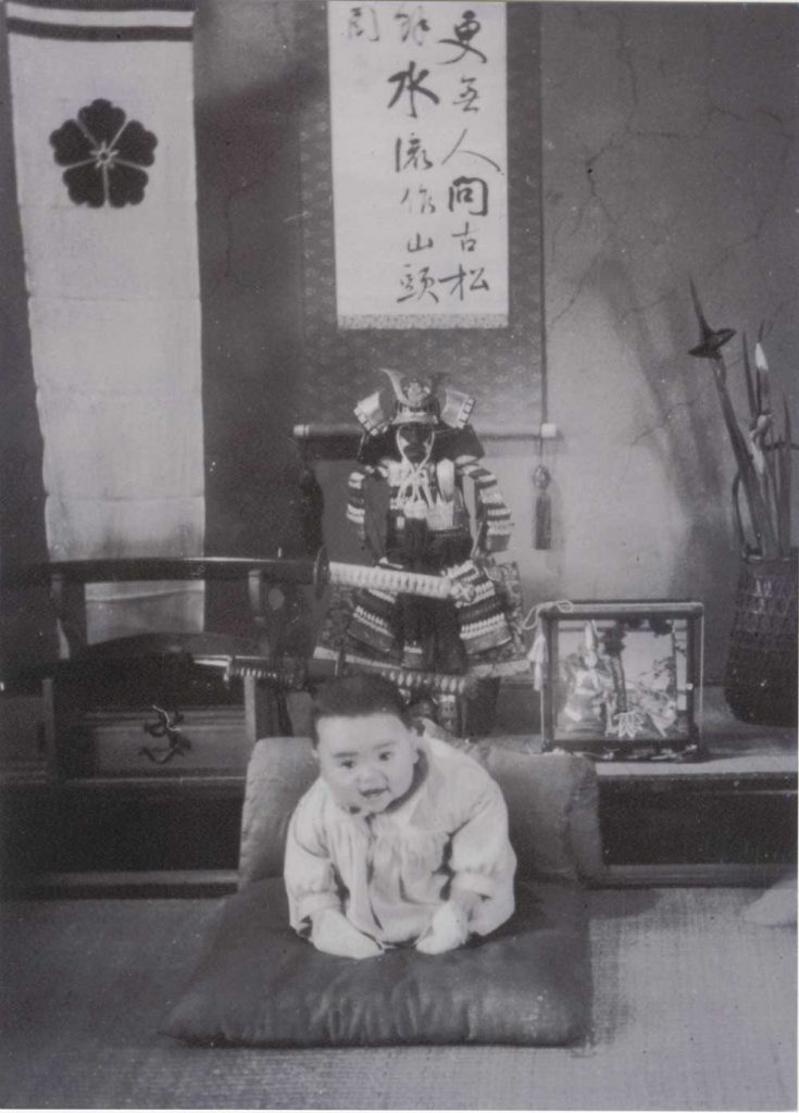 Unidentified photographer, [Kazuo Ishiguro as a baby in front of family samurai heirlooms, Nagasaki], ca. 1955. Gelatin silver print, 20.3 x 15 cm. Harry Ransom Center Kazuo Ishiguro Papers.