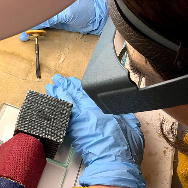 Conservators painstakingly remove glue that binds