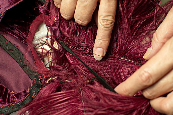 Ostrich feathers in burgundy ball gown from Gone With The Wind, here being repaired by Cara Varnell, independent art conservator (2011). Harry Ransom Center, University of Texas at Austin. Photo by Pete Smith.