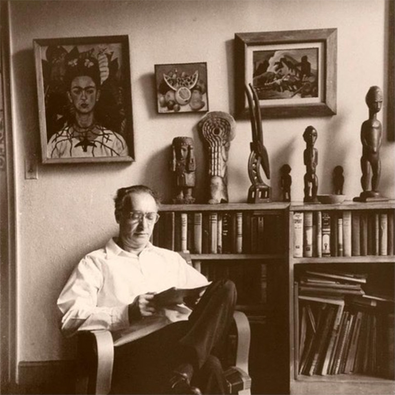 Nickolas Muray seated in front of Frida Kahlo's self portrait