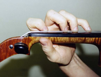 Proper violin / viola hand position from the instrument side, showing fingers on the string, neck of the instrument, and thumb.