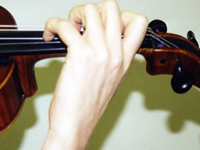 Proper violin / viola hand position from the hand side, showing back of the hand with fingers placed properly on the string.