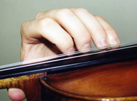 Proper violin / viola hand position from the instrument side, showing fingers on the string in a higher position, curved over the body of the instrument.
