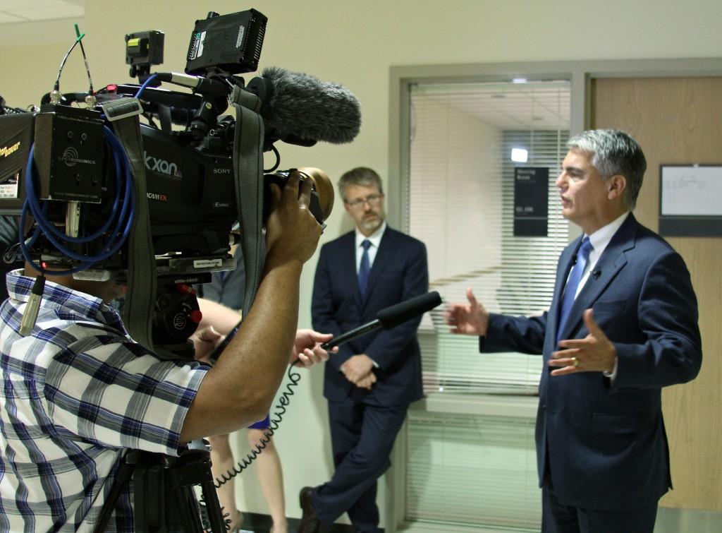 Chris Brownson, CMHC director, watches President Fenves get interviewed.