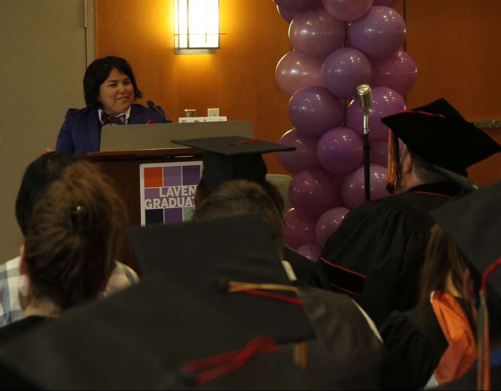 Elisa Ramos (Office of the Dean of Students) addresses students as master of ceremonies during Lavender Graduation.