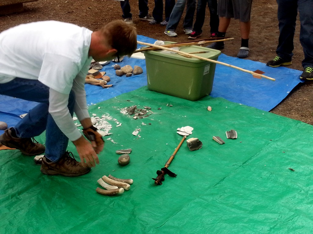 "Chris displaying for attendees the different types of ""billets"" that would have been used for knapping (parts of the knapper's kit).  They include deer antler ""billets"" of various sizes for soft percussion and fist-sized ""hammer stones"" for hard percussion work."