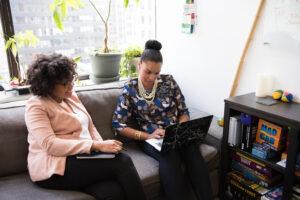 Canva-Two-Women-Sitting-on-Black-Sofa