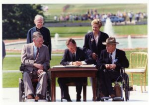 President H. W. Bush sits at a desk in the Rose Garden with two men using wheelchairs to sign the ADA
